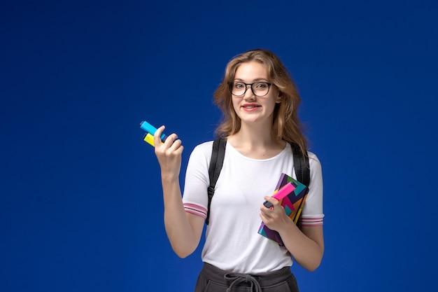 Vooraanzicht van vrouwelijke student in wit overhemd die rugzak draagt en voorbeeldenboek met viltstiften op de blauwe muur houdt