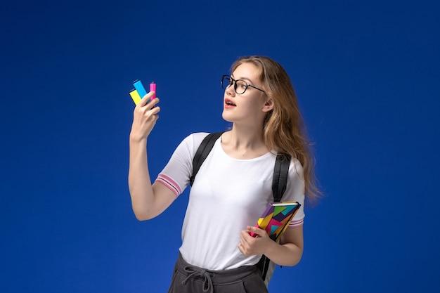 Vooraanzicht van vrouwelijke student in wit overhemd die rugzak draagt en voorbeeldenboek op de blauwe muur houdt