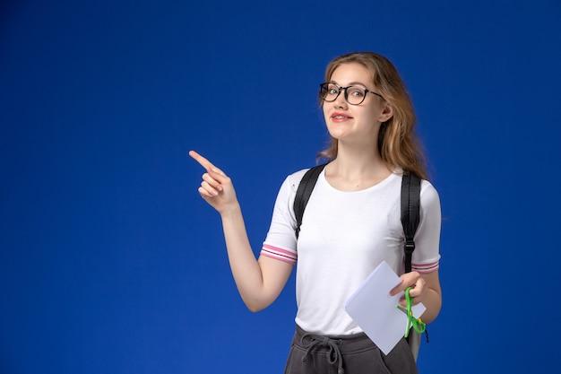 Vooraanzicht van vrouwelijke student in wit overhemd die rugzak dragen en document en schaar houden die op blauwe muur glimlachen