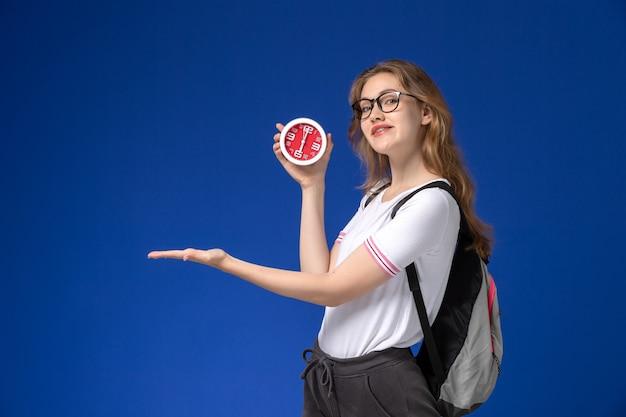 Vooraanzicht van vrouwelijke student in wit overhemd die rugzak dragen en klokken op blauwe bureau vrouwelijke universiteitsles houden