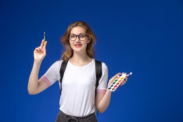 Vooraanzicht van vrouwelijke student in wit overhemd die rugzak dragen en kunstverfborstel houden die op de blauwe muur glimlachen