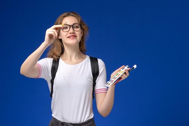 Vooraanzicht van vrouwelijke student in wit overhemd die rugzak dragen en kunstverfborstel op blauwe muur houden