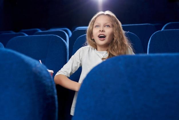 Vooraanzicht van vrouwelijke tiener kijken naar actiefilm in de bioscoop