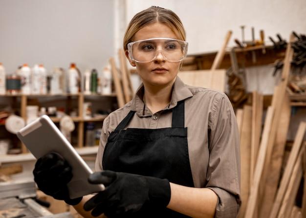 Vooraanzicht van vrouwelijke timmerman die met veiligheidsbril tablet houdt
