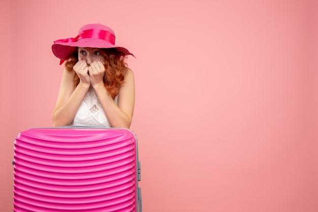 Vooraanzicht van vrouwelijke toerist met roze zak die op roze muur wordt doen schrikken