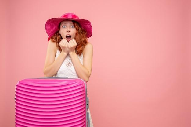 Vooraanzicht van vrouwelijke toerist met roze zak met geschokt gezicht op roze muur