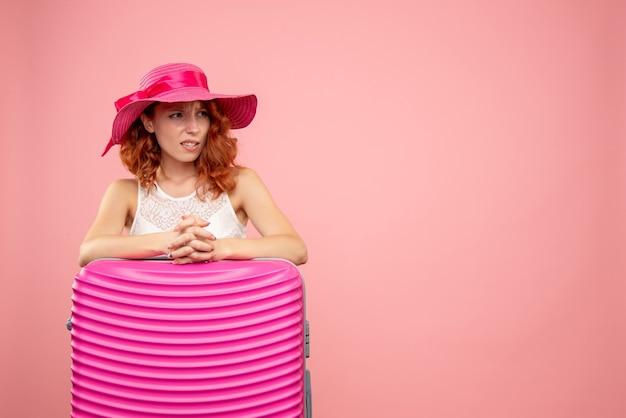 Vooraanzicht van vrouwelijke toerist met roze zak op de roze muur