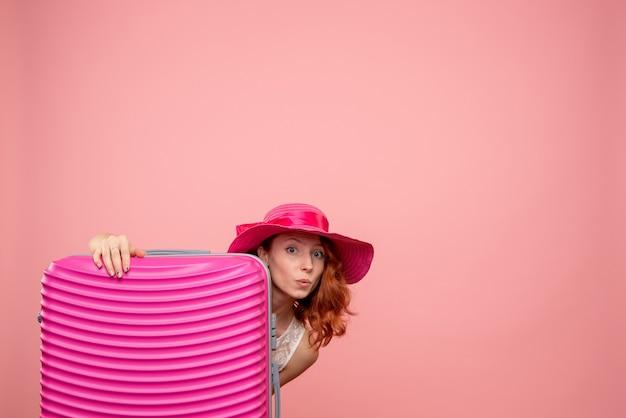 Vooraanzicht van vrouwelijke toerist met roze zak op de roze muur Gratis Foto