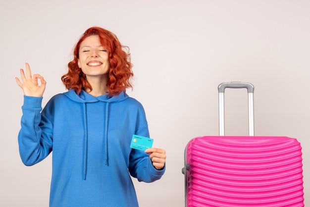 Vooraanzicht van vrouwelijke toerist met roze zak op witte muur