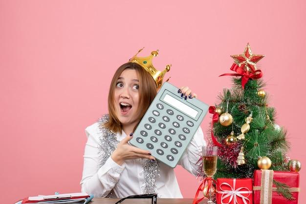 Vooraanzicht van vrouwelijke werknemer in de calculator van de kroonholding op roze