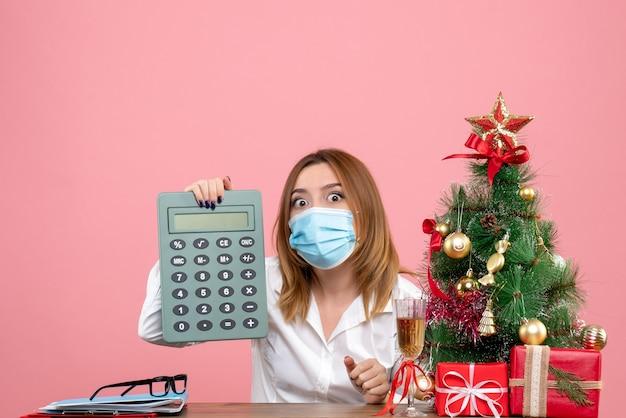 Vooraanzicht van vrouwelijke werknemer in de steriele calculator van de maskerholding op roze