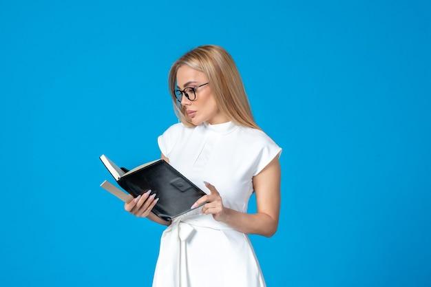 Vooraanzicht van vrouwelijke werknemer in mooie witte jurk met notitieblok op blauwe muur
