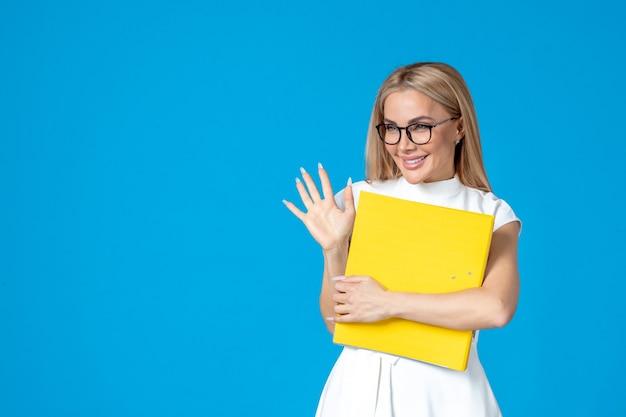 Vooraanzicht van vrouwelijke werknemer in witte jurk die map vasthoudt en iemand begroet op blauwe muur