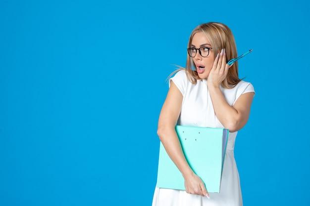 Vooraanzicht van vrouwelijke werknemer in witte jurk met blauwe map op blauwe muur