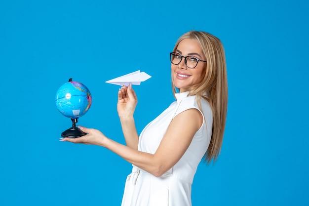 Vooraanzicht van vrouwelijke werknemer in witte jurk met earth globe en papieren vliegtuigje op blauwe muur