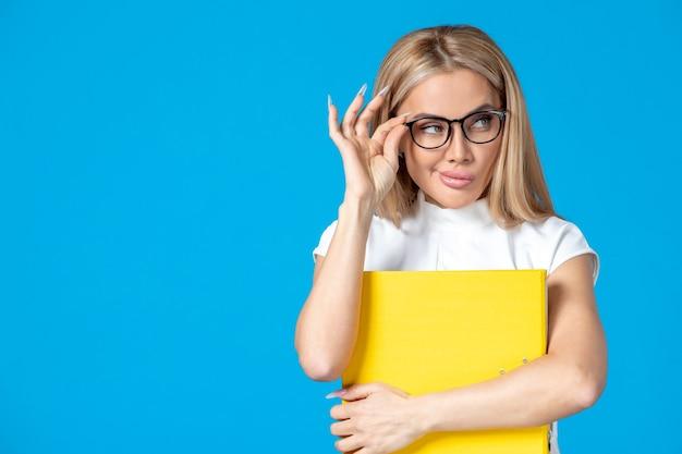 Vooraanzicht van vrouwelijke werknemer in witte jurk met gele map op blauwe muur