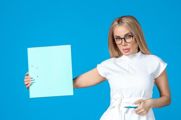 Vooraanzicht van vrouwelijke werknemer in witte jurk met map op blauwe muur