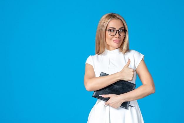 Vooraanzicht van vrouwelijke werknemer in witte jurk poseren met notitieblok op blauwe muur