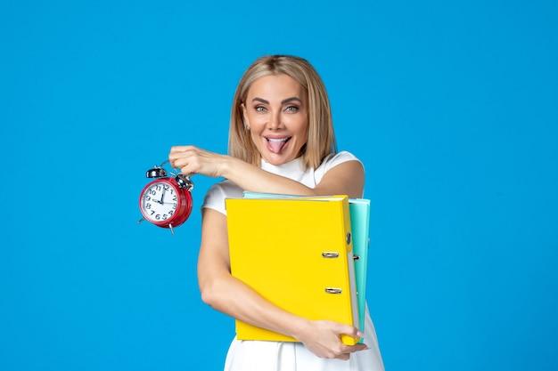 Vooraanzicht van vrouwelijke werknemer met map en klok op blauwe muur