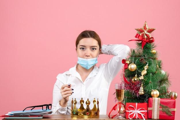 Vooraanzicht van vrouwelijke werknemer zittend in steriel masker op roze