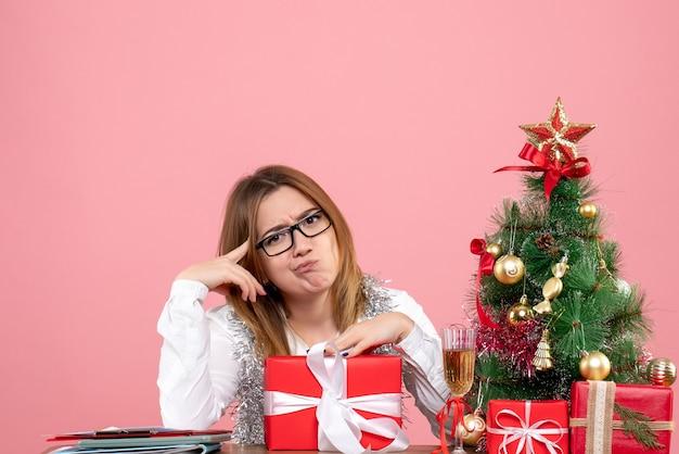 Vooraanzicht van vrouwelijke werknemer zittend rond kerstcadeautjes en boom op roze