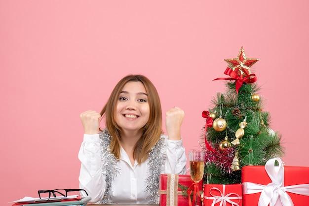 Vooraanzicht van vrouwelijke werknemer zittend rond kerstcadeautjes op roze