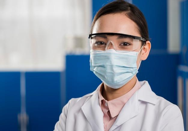 Vooraanzicht van vrouwelijke wetenschapper met medische masker