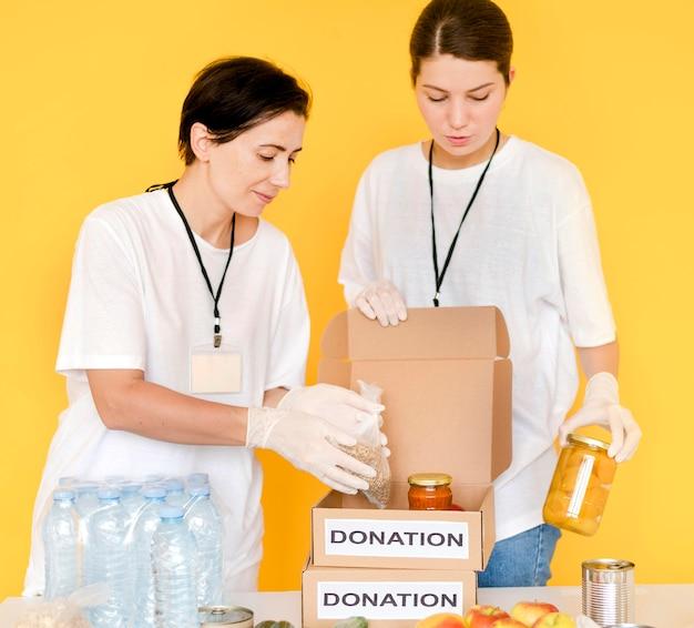 Vooraanzicht van vrouwen die voedsel in schenkingsdoos zetten