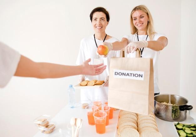 Vooraanzicht van vrouwen die voedsel schenken