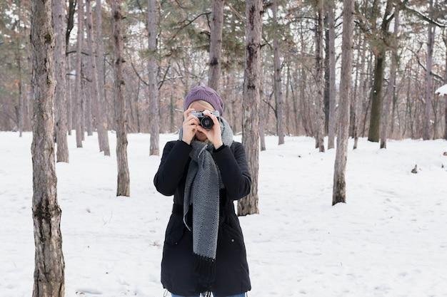 Vooraanzicht van vrouwenfotograaf met camera in de winter Gratis Foto