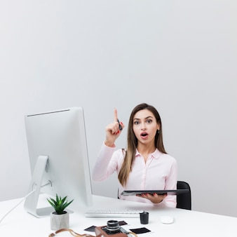 Vooraanzicht van vrouwenzitting bij bureau en het hebben van een idee
