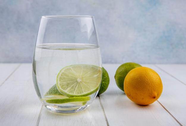 Vooraanzicht van water in een glas met limoen en citroen op een wit oppervlak