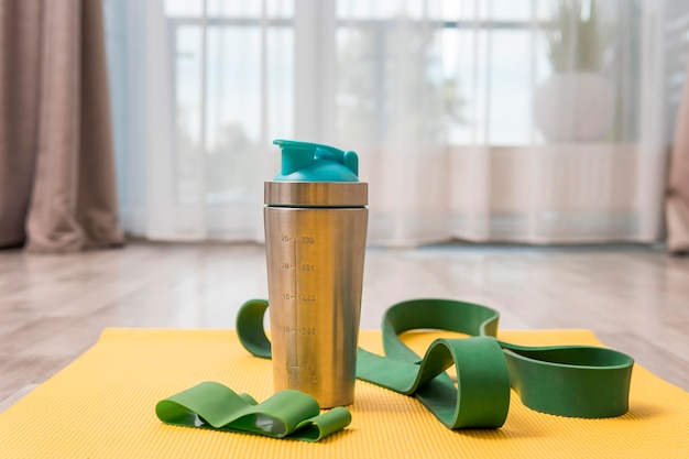 Vooraanzicht van waterfles en elastische band om thuis te trainen