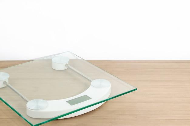 Vooraanzicht van weegschaal op houten tafel en witte achtergrond