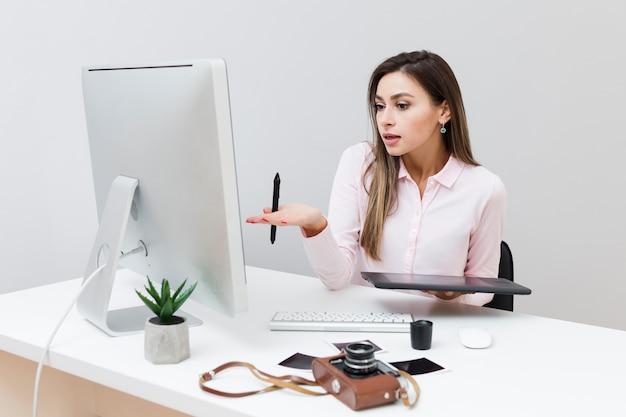 Vooraanzicht van werkende vrouw die computer bekijkt en niet begrijpt wat er aan de hand is