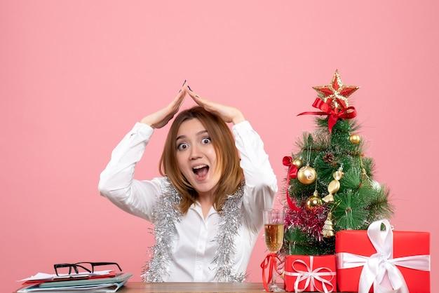 Vooraanzicht van werkneemster achter haar tafel met cadeautjes op roze