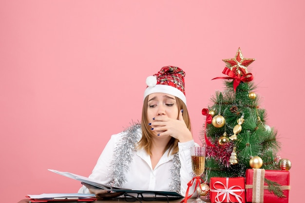 Vooraanzicht van werkneemster die documenten controleert die zich moe voelen op roze