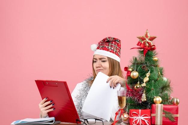 Vooraanzicht van werkneemster die documenten op roze controleert
