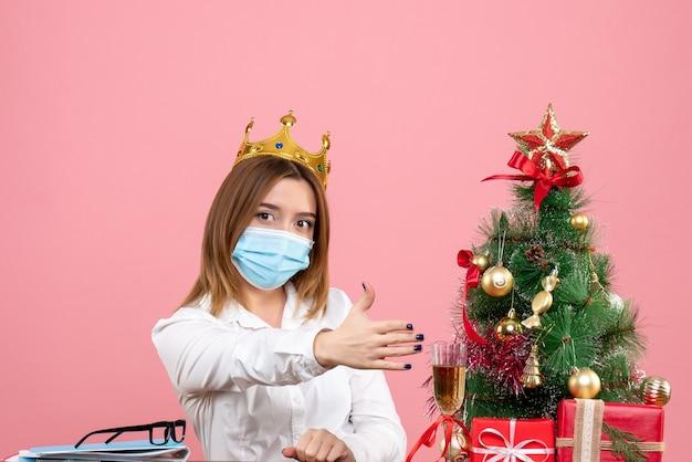 Vooraanzicht van werkneemster in steriel masker met kroon op roze