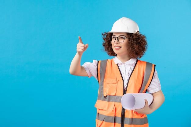 Vooraanzicht van werkneemster in uniform op de blauwe muur