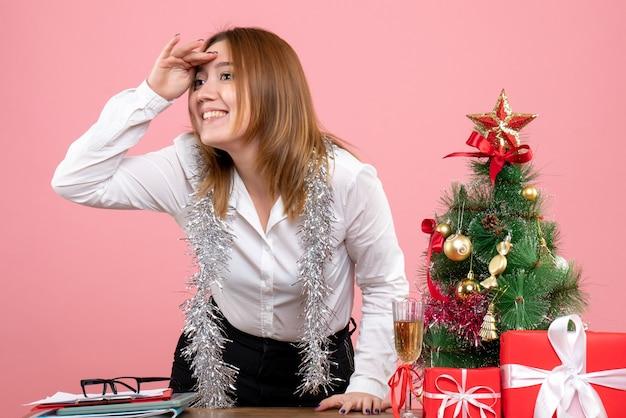 Vooraanzicht van werkneemster rond kerstcadeautjes afstand kijken op roze