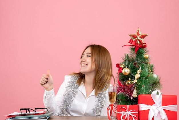 Vooraanzicht van werkneemster zittend achter haar tafel lachend op roze
