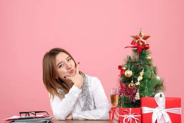 Vooraanzicht van werkneemster zittend achter haar tafel op roze