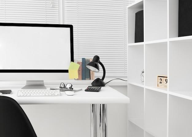 Vooraanzicht van werkruimte met computerscherm en lamp