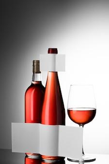 Vooraanzicht van wijnglas en duidelijke flessen met blanco etiketten