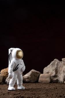 Vooraanzicht van witte astronaut met verschillende rotsen op maan kosmische sci fi-fantasie