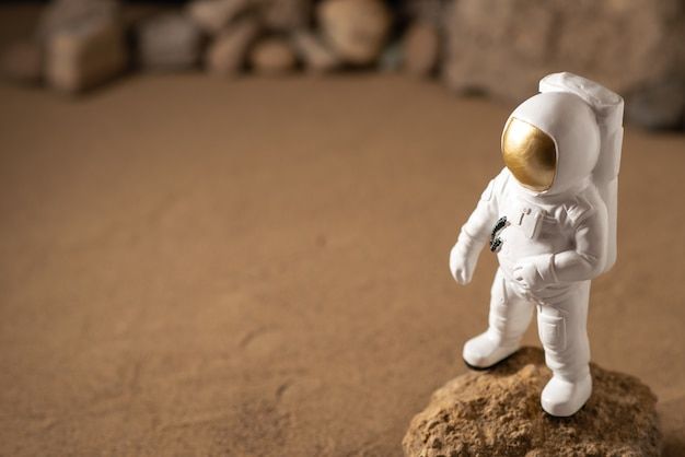 Vooraanzicht van witte astronaut rond stenen op zwart