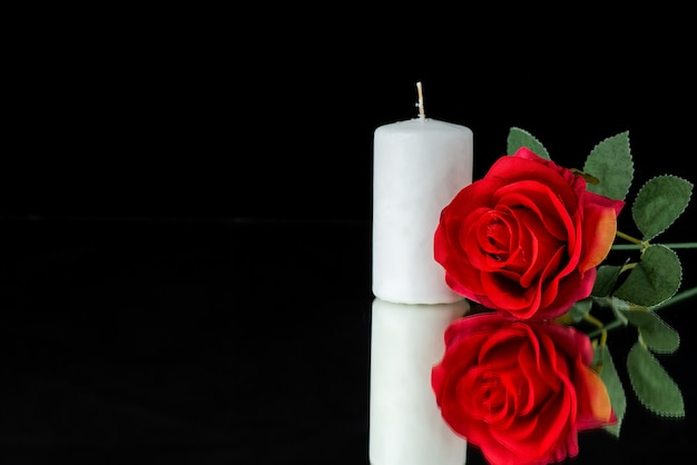 Vooraanzicht van witte kaars met rode roos op zwart