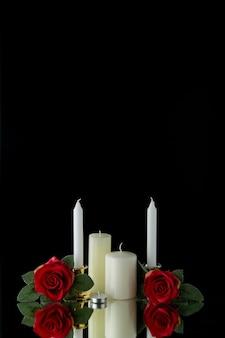 Vooraanzicht van witte kaarsen met rode bloemen op zwarte muur