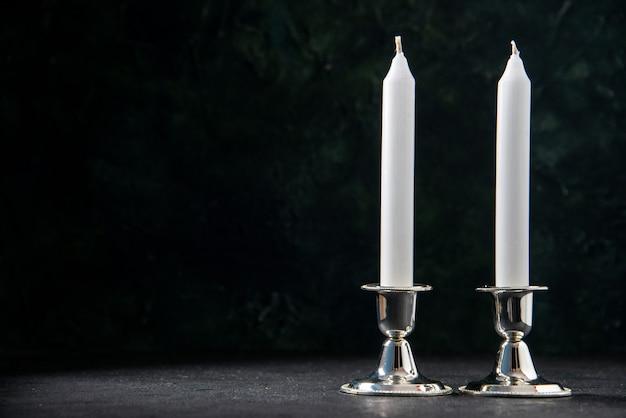 Vooraanzicht van witte lange kaarsen op de donkere muur